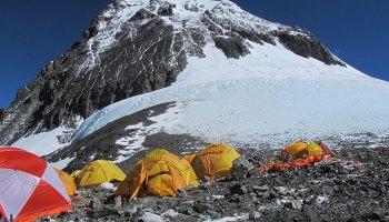 Tiendas de campaña debajo de la cima con nieve del Everest.