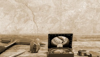 Rock pick, compass, and other tools of geology on a table with a map in the background