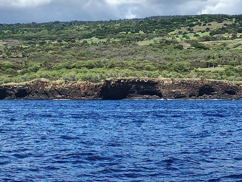 View from the water of lava tubes along the coast of Hawaiʻi near Hualalai volcano