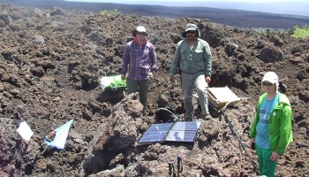 A group of researchers attend to seismic instruments at Sierra Negra in the Galápagos.