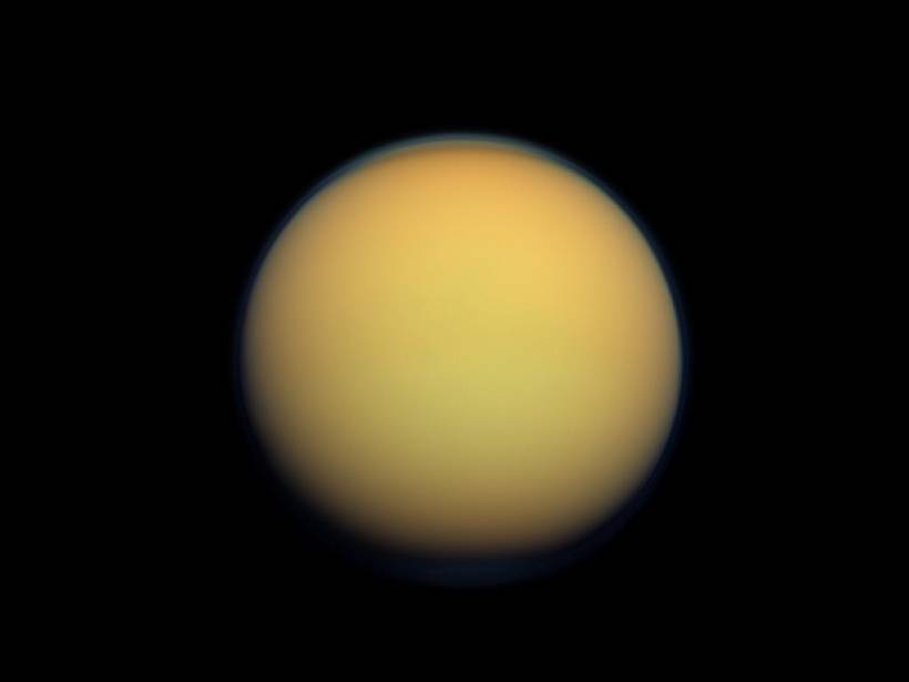 A natural color image of Titan, which looks like a fuzzy orange ball set in a black background