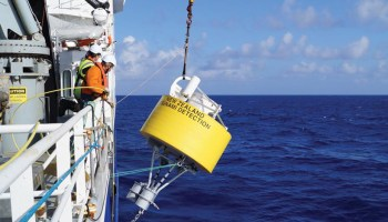 A yellow DART buoy being lowered overboard
