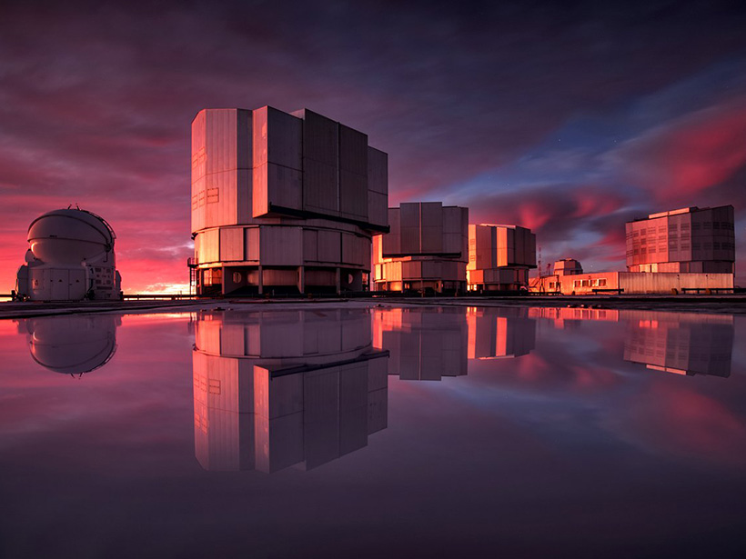 Several large telescopes are reflected in water at sunset at a mountaintop observatory in Chile.