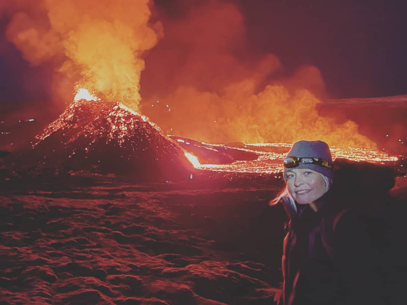 Photo of Icelandic Meteorological Office seismologist Kristín Jónsdóttir in the foreground, with erupting Fagradalsfjall in the background. As bright orange lava spills out of the small crater and flows behind her, eerie orange-tinged smoke billows into the air. The ground of solidified black basalt glows red.