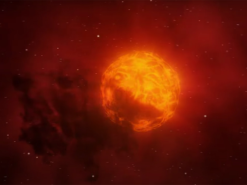 The supergiant Betelgeuse glows red and orange against a dark, starry background. The star's surface is mottled and emits a faint reddish glow representing its stellar wind. A dark cloud of dust partially obscures the star's lower left region.