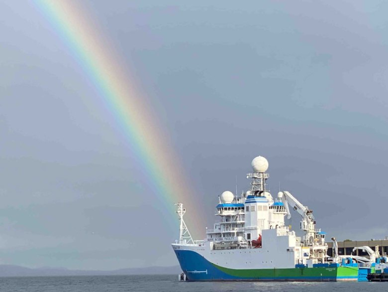A large ship sits in the water docked at port with a rainbow in the background