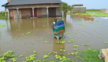 Image of a person carrying plastic chairs through floodwaters in Buliisa, Uganda