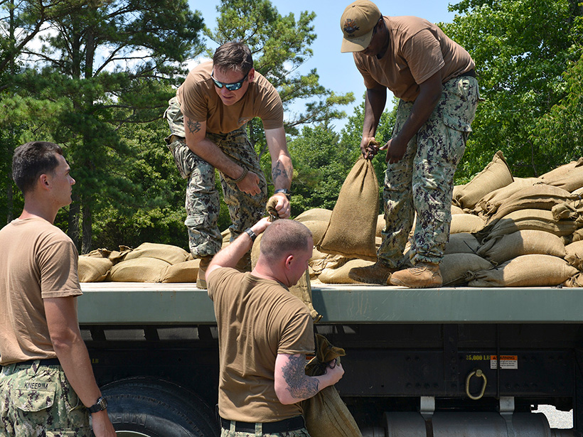 Men in military uniforms unload sandbags from the back of a truck.
