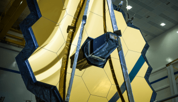 A close-up view of the grid of hexagonal golden mirrors that make up the primary mirror of the James Webb Space Telescope.