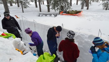 Students and researchers performing measurements in a snow pit excavated to the ground in Grand Mesa, Colo.