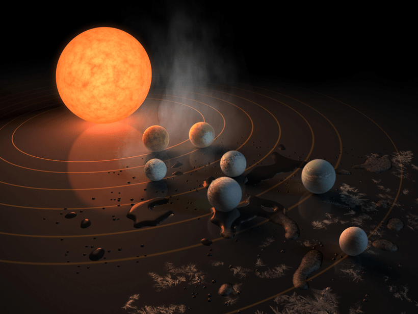 An artist's rendering shows the seven small rocky worlds of the TRAPPIST-1 system in orbit around an M dwarf star.