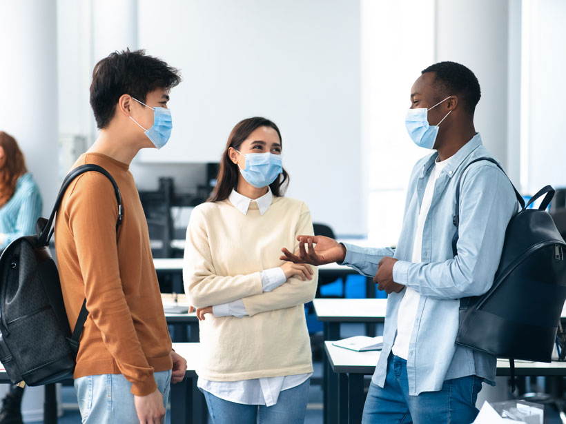 Three college students in face masks talk in a classroom.