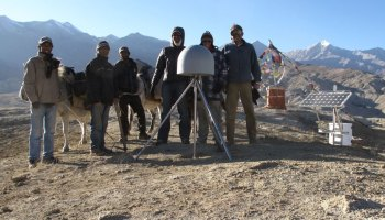 Research scientists pose in the Himalayas with a GNSS station.
