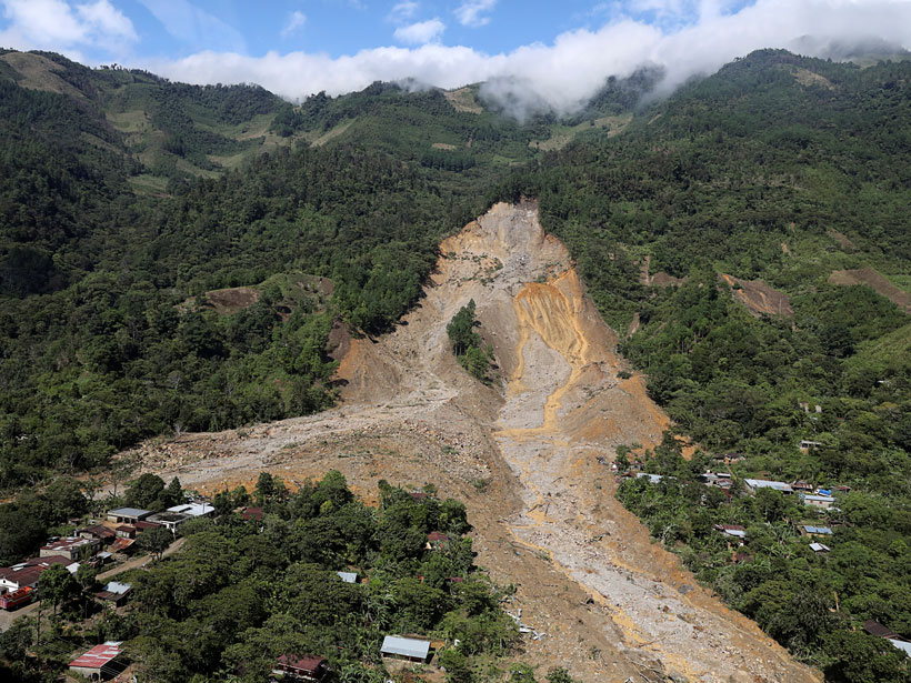 Aerial view of a large mudslide that flowed down a forested hillslope and into a small community