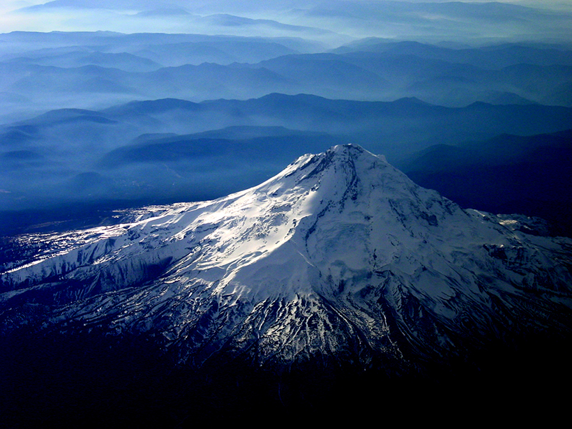 Aerial view of snowcapped Mount Hood with lower-lying mountains and fog in the background