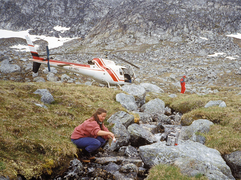 Researchers collect sediments from a rocky stream with a helicopter and steep rock hills in the background