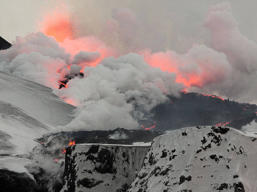 Snow-covered Fimmvörðuháls, close to Eyjafjallajökull, where white ash and steam are tinged red by lava erupting from a fissure