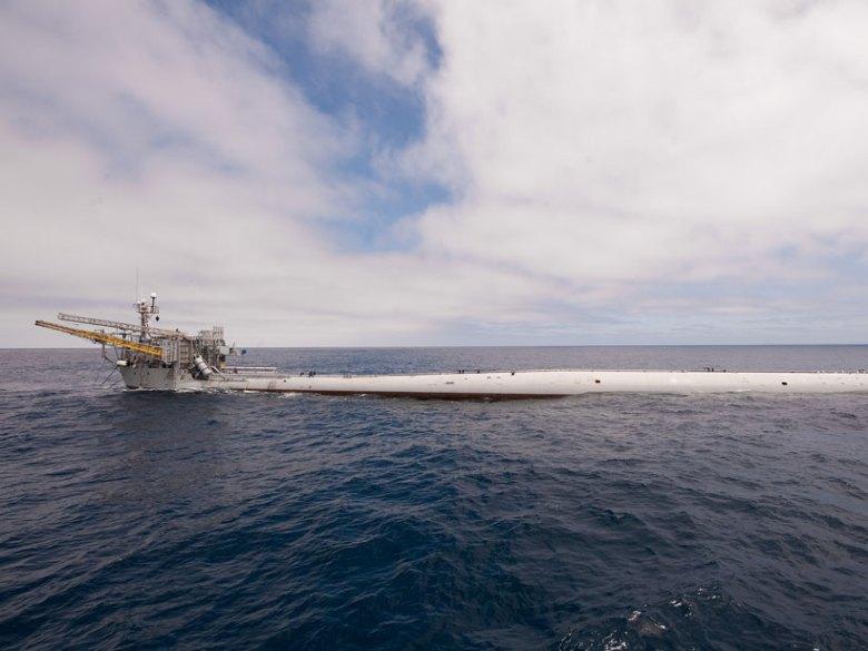 The long, tubular research platform FLIP lies horizontally at the ocean surface.