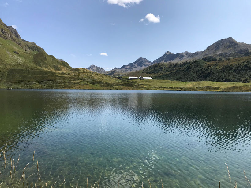 Lake Cadagno—an alpine lake in Switzerland with calm blue-green waters surrounded by sharp-peaked mountains