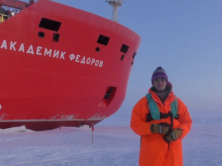 Sea ice researcher Robbie Mallett stands on perennial sea ice next to the Russian research vessel Akademik Fedorov.
