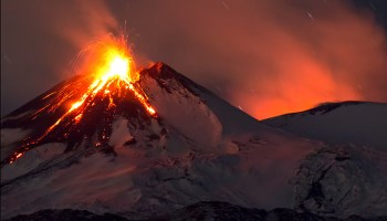 Mount Etna, a stratovolcano, sits in front of an ashy night sky. Lava erupts from and flows down the volcano, and ash and gas billow up from a vent behind the peak and make the sky glow orange. A few star trails appear in the upper right corner.