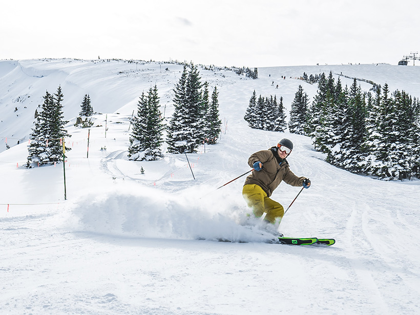 A downhill skier is mid-turn, throwing up snow beneath his angled skis.