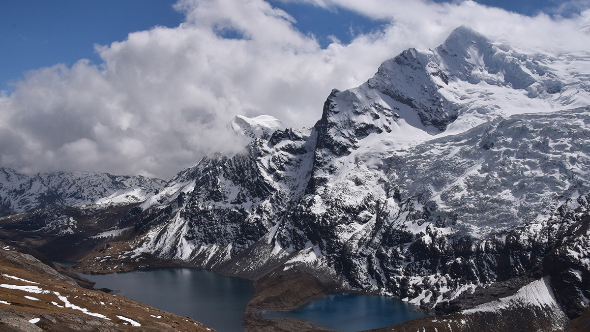 A glacier- and snow-covered high mountain peak with glacial lakes