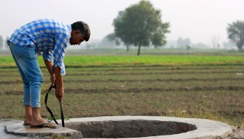 A young man pulls water from a well in an agricultural area in India.
