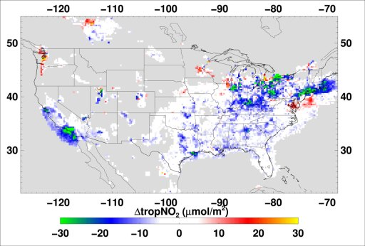 A gray map of the continental United States, with splotches of color ranging from green to yellow over primarily urban regions. A scale bar is at the bottom of the map, ranging from −30 to 30 micromoles per square meter of change in tropospheric NO2.