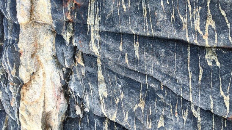 A close-up view of a black, crystalline rock with white bands of varying thicknesses running through it. A boot is in the upper right corner, showing the scale of the rock.