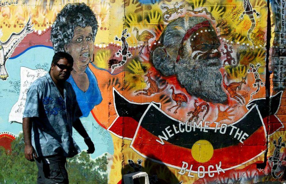 Un aborigen australiano pasa por delante de un mural de arte indígena en Redfern, un barrio periférico de Sidney