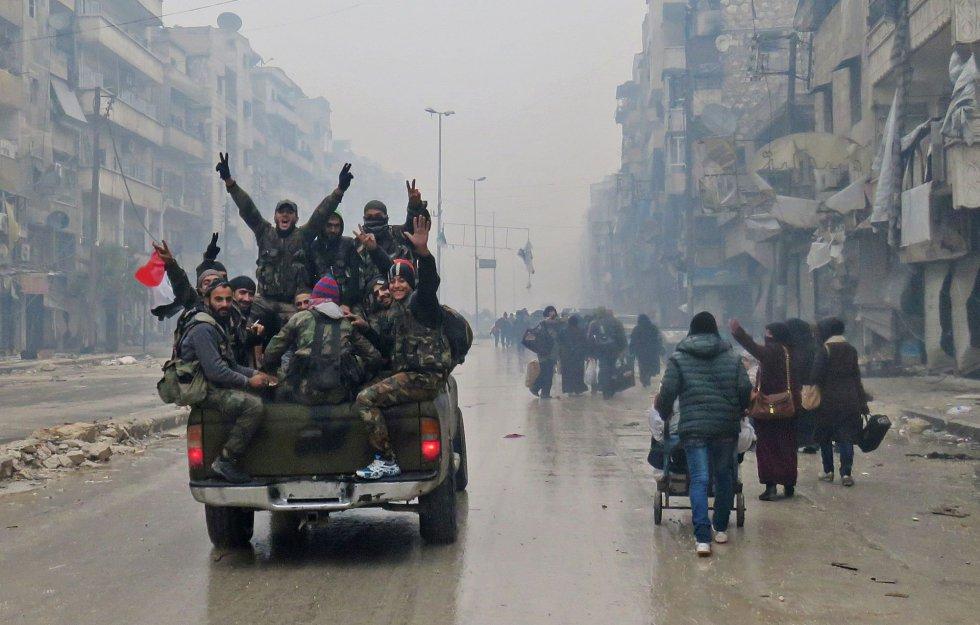 Guerrilleros sirios a favor del régimen gesticulan mientras conducen por el vecindario de Bustan al-Qasr, en el barrio de Fardos de Alepo, después de que retomaran el control del área que defendían los insurrectos durante más de cuatro años, el 13 de diciembre.