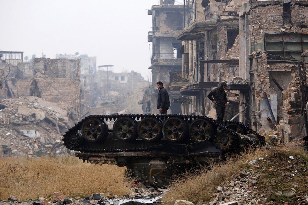 Civiles atrapados en los barrios que quedan en poder de los rebeldes y que están asediados por el ejército sirio en el este en la ciudad de Alepo lanzaron hoy llamamientos desesperados de ayuda para que alguien salve sus vidas. En la imagen, fuerzas leales al presidente de Siria, Bachar el Asad, inspeccionan un tanque dañado, en Alepo el13 de diciembre.