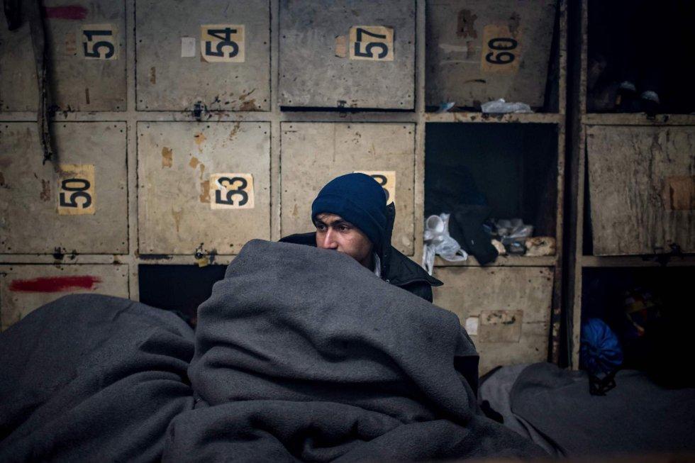 """En cuanto a Grecia, la organización señala que """"miles"""" de personas permanecen en campamentos superpoblados y luchan contra temperaturas por debajo de cero grados. En la imagen, un migrante intenta protegerse del frío en Belgrado (Serbia)."""