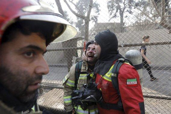 Bomberos iraníes reaccionan al saber que varios de sus compañeros quedaron atrapados en el derrumbe que siguió a un grave incendio en el edificio Plasco en Teherán.