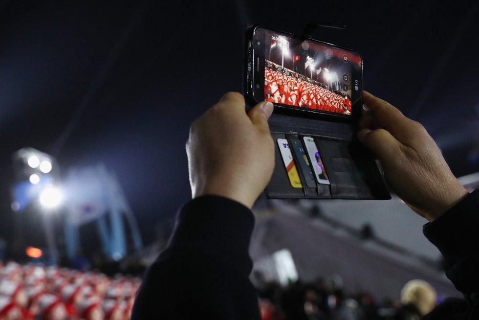 Un espectador graba con su movil actuaciones previas a la ceremonia de inauguración de los Juegos Olímpicos de Invierno 2018 de PyeongChang (Corea del Sur), el 9 de febrero de 2018.