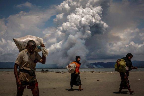 Nuvem de fumaça sobe na fronteira com Mianmar, enquanto refugiados rohingyas caminham pela costa depois de terem conseguido cruzar para Bangladesh de barco pela Baía de Bengala, em Shah Porir Dwip (Bangladesh), em 11 de setembro de 2017.