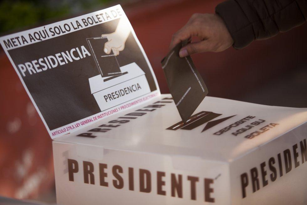 Un hombre deposita su voto en una urna electoral.