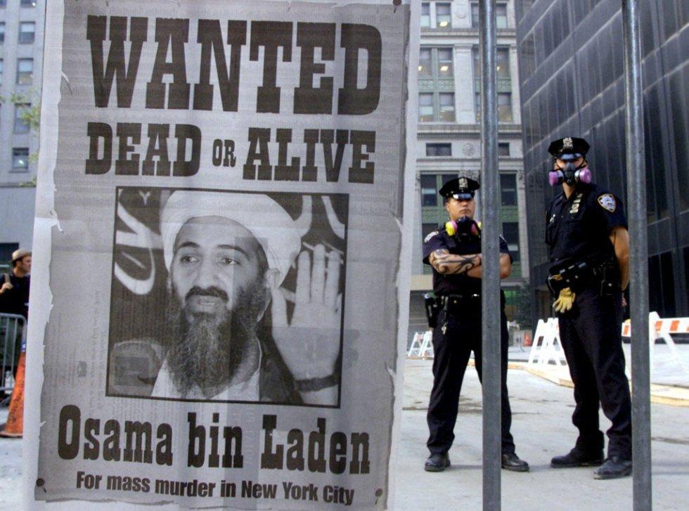 """Dos policías al lado de un cartel repartido por un diario de Nueva York, del 18 de septiembre, que pide la captura de Osama Bin Laden, con el lema: """"Se busca muerto o vivo"""", tras el ataque terrorista del 11 de septiembre a las Torres Gemelas de Nueva York y al Pentágono, en Washington."""
