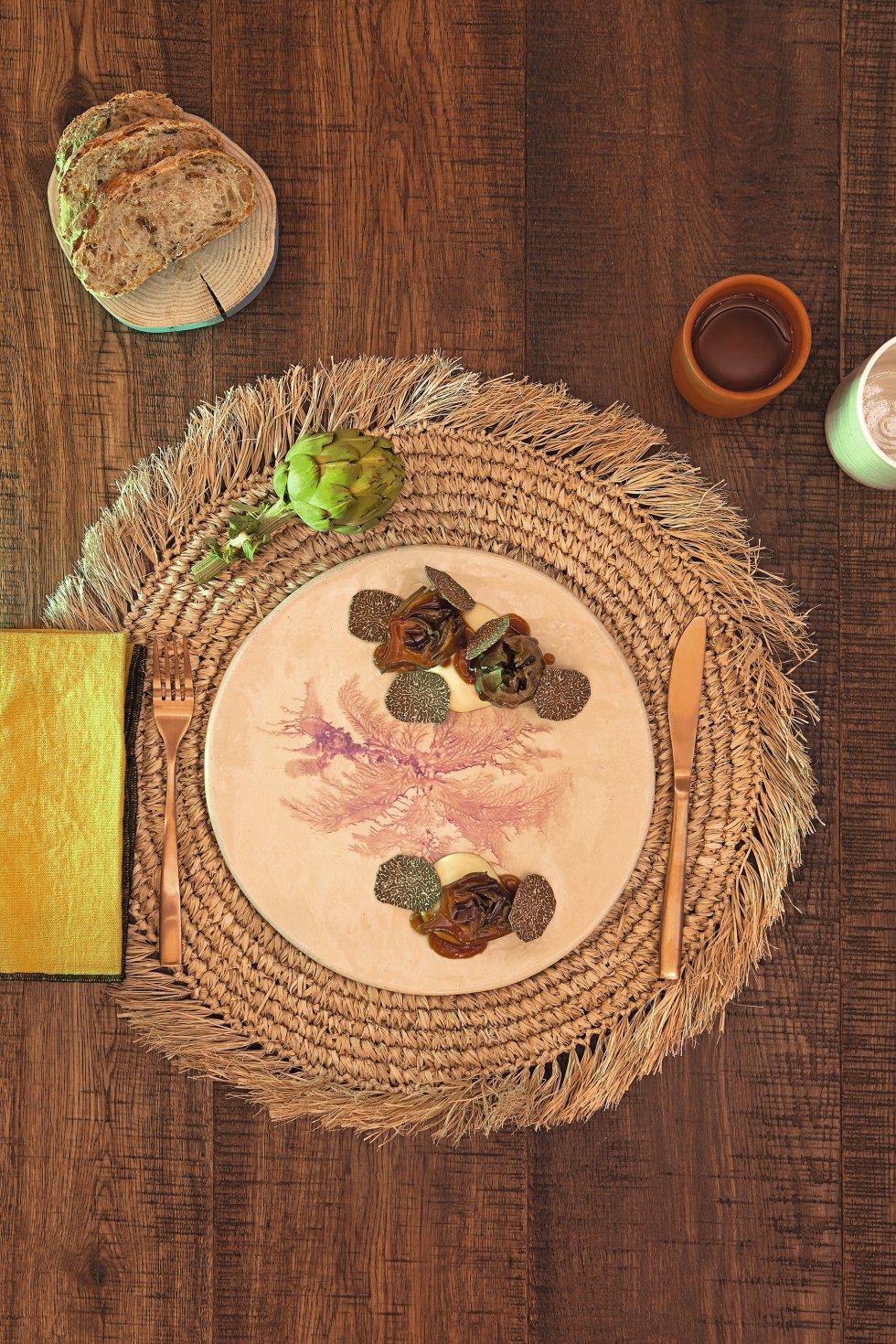 ALCAHOFAS CON TRUFA Y CREMOSO DE RAÍCES     Ingredientes.  Para cuatro personas: Para las alcachofas: 500 gramos de algas (kombu o lechuga de mar, por ejemplo), 5 litros de agua, 15 alcachofas. Para el aceite de guindilla: 1 guindilla, 100 gramos de aceite de oliva. Para el jugo: 1 kilo de garbanzos puestos en remojo ocho horas en agua tibia y sal, 1 kilo de zanahorias, 1 kilo de cebollas, 15 gramos de tamari o soja sin gluten. Para el puré de patata: 200 gramos de patata ratte, 20 gramos de leche vegetal, aceite de oliva virgen extra, 5 gramos de sal. Para la terminación: 1 trufa negra.     Elaboración.   Las alcachofas: 1. Infusionar las algas con agua durante 15 minutos a fuego vivo. Una vez hervidas, colar y reservar. 2.Limpiar las alcachofas cuidadosamente aprovechando parte del tallo. Introducirlas en el agua de cocer las algas. Cuando vuelva a arrancar el hervor, retirarlas del fuego y dejar que se enfríen en la misma agua. El aceite picante: 3.Verter el aceite en una sartén. Cuando esté caliente, agregar la guindilla picada sin las pepitas. 4. Dorar el chile y retirar del fuego. Dejar en la sartén hasta que enfríe y después colar. El jugo vegetal: 5.Poner todos los ingredientes a hervir a fuego lento durante 6 horas. 6. Colar, añadir el tamari y reducir hasta obtener una textura densa. El puré de patata: 7. Envolver las patatas en papel de aluminio y cocinar en el horno a 210 grados durante 20 minutos. 8. Cuando aún esté caliente la patata, pasarla por el pasapuré y después por un tamiz fino. 9. Poner la patata tamizada en un cazo junto a la leche y la sal. Batirla para mezclarla e incorporar el calor (es mejor en una plancha que sobre el fuego directo). 10. Añadir el aceite de oliva virgen extra. Rectificaremos de sal si es necesario. Antes de servir el plato: 11. Freír las alcachofas a 180 grados. Cuando estén doradas, sacar y escurrir el aceite sobrante con un papel de cocina absorbente. Presentación: 12. Poner en el plato una base de puré de patata. Sobr