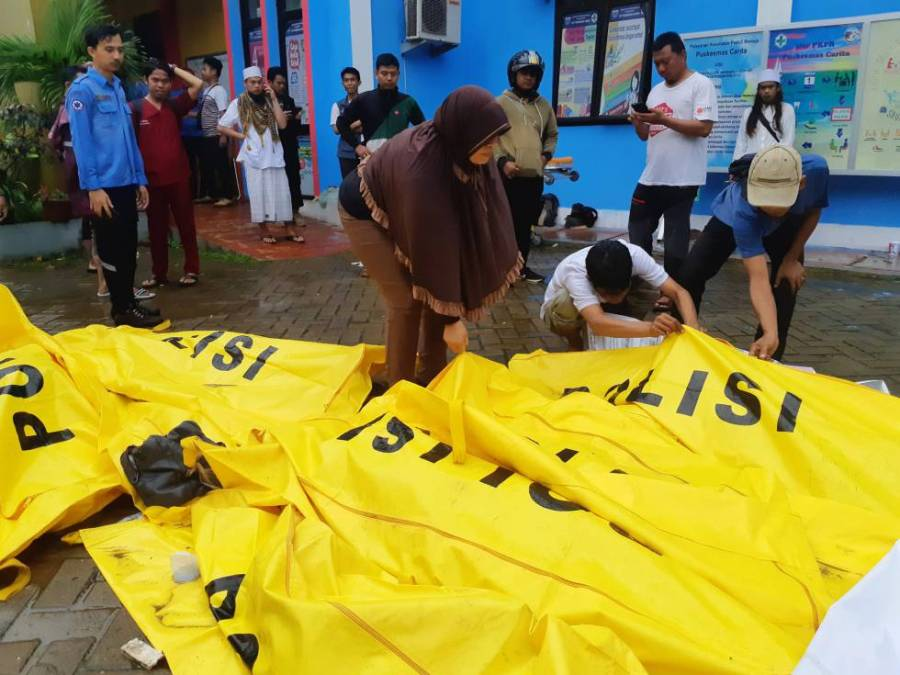 Vecinos de Pandeglang (Indonesia) inspeccionan varios cadáveres en busca de sus familiares desaparecidos.