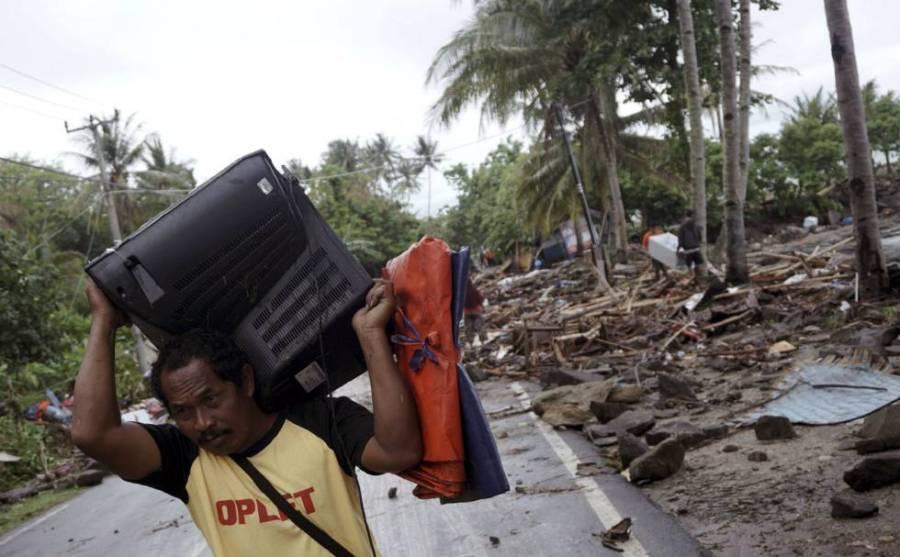 Un hombre salva su televisión después de que un tsunami sacudiera Anyer (Indonesia).