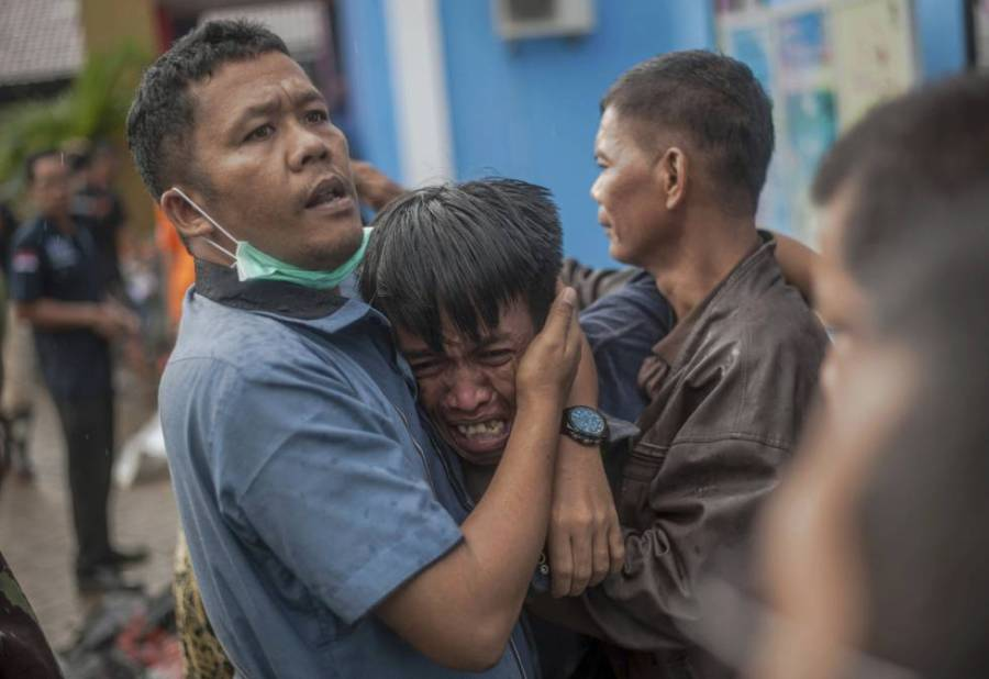 Un hombre llora tras encontrar el cadáver de un familiar en Carita (Indonesia).