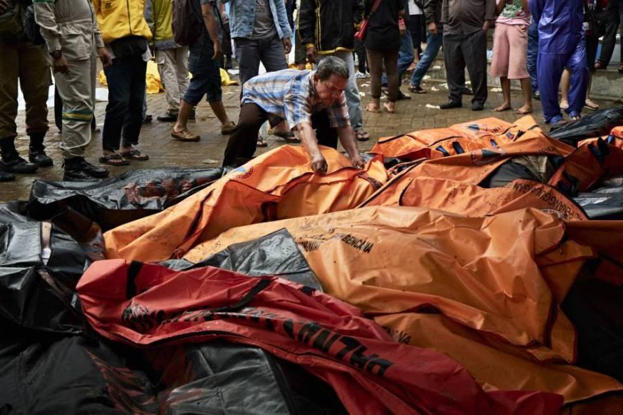 Un hombre mira entre las bolsas con los cuerpos de las víctimas del tsunami en una morgue improvisada en Carita (Indonesia).
