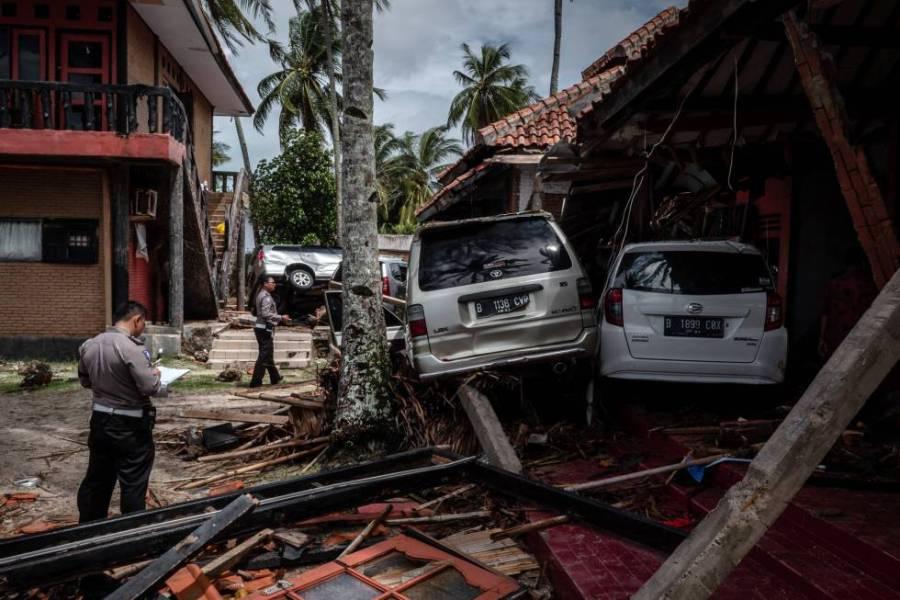 Personal de emergencias junto a varios vehículos siniestrados en una calle de la localidad de Carita (Indonesia) tras el paso del tsunami, el 24 de diciembre de 2018.