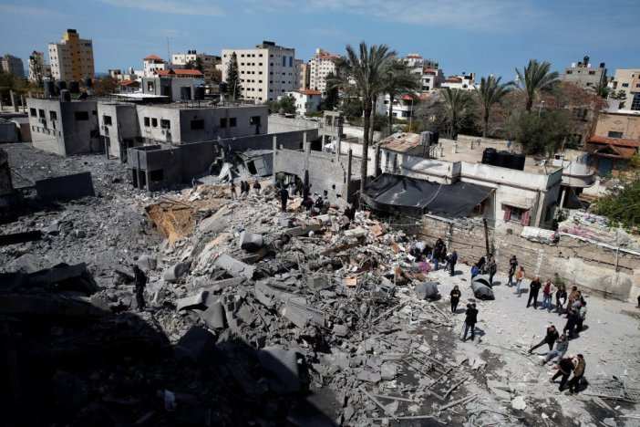 Un grupo de palestinos inspecciona una sede de Hamás después de ser destruida en un ataque aéreo por las fuerzas israelíes. La escalada bélica se ha detenido antes del amanecer, según residentes en la Franja.