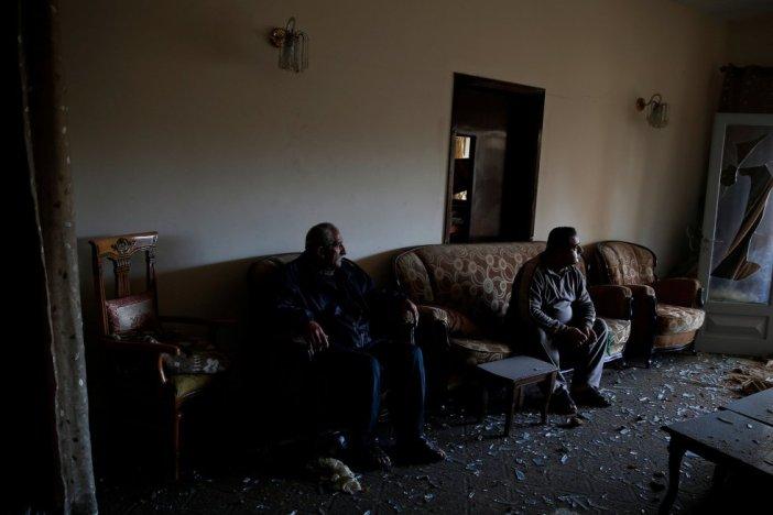 Dos hombres palestinos descansan en el interior de su casa, destruida tras los bombardeos israelíes, la madrugada de este martes. Los lanzamientos se produjeron entre las 22.00 del lunes y las 3.15 del martes, según el diario 'Jerusalem Post', sin que se hayan producido víctimas.