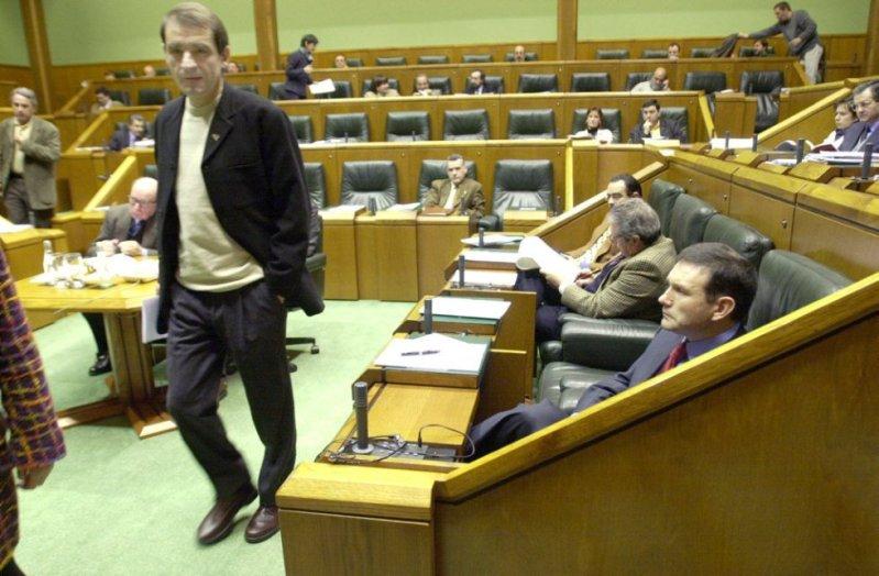 Josu Ternera, parlamentario de Euskal Herritarrok, pasa frente al lehendakari Juan José Ibarretxe (sentado), durante un pleno sobre la violencia de ETA en 2000.