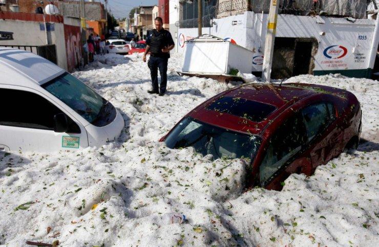 Aunque las granizadas son usuales en esta temporada del año, no se tiene registro de una tan fuerte como la de este domingo. En la imagen, un policía junto a varios vehículos sepultados por el granizo en la ciudad de Guadalajara (México).