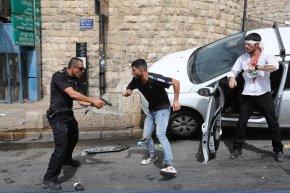 Un policía apunta con un arma a un palestino, junto a un judío ortodoxo herido que estrelló su automóvil cerca de la Puerta de los Leones, este lunes. El Fondo de Naciones Unidas para la Infancia (Unicef) ha denunciado este domingo que hasta 29 niños han resultado heridos en los disturbios entre manifestantes palestinos y la policía israelí en Jerusalén Este, mientras que hasta ocho menores habrían sido detenidos.